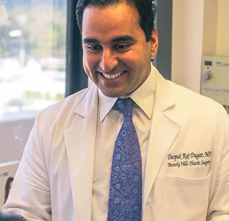 Dr. Deepak Dugar, best plastic surgeon in Beverly Hills, CA smiling to a patient