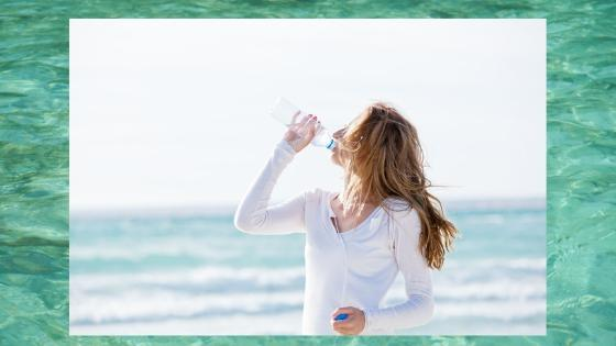 a woman on the beach drinking a bottled water