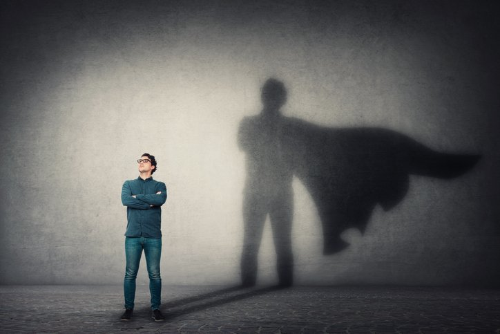 a grounded person casting a superhero with cape shadow on the wall