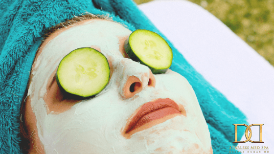 young woman with cucumber slices on eyes and facial cream