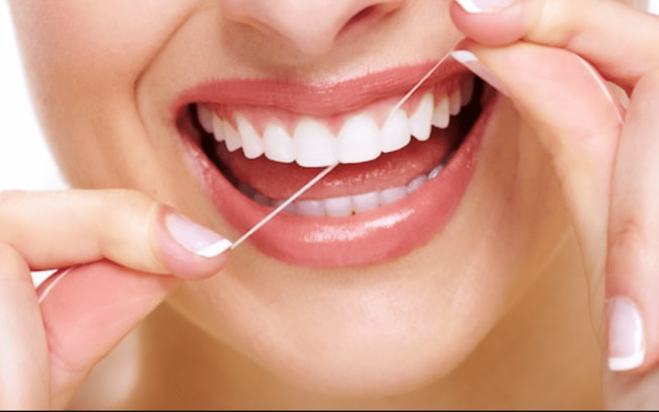 close-up of a perfect smile while using dental floss