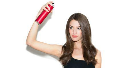 beautiful woman applying hair spray on her hair