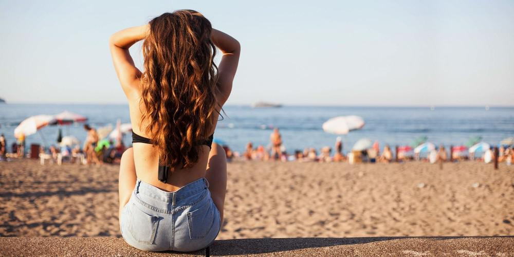 woman with a surfer hair sitting on the beach facing the ocean