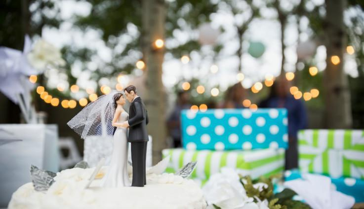 wedding cake with toppers of a couple leaning for a kiss