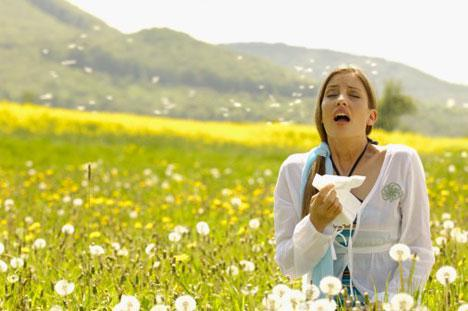 Young girl on a flower garden sneezing and holding tissue paper