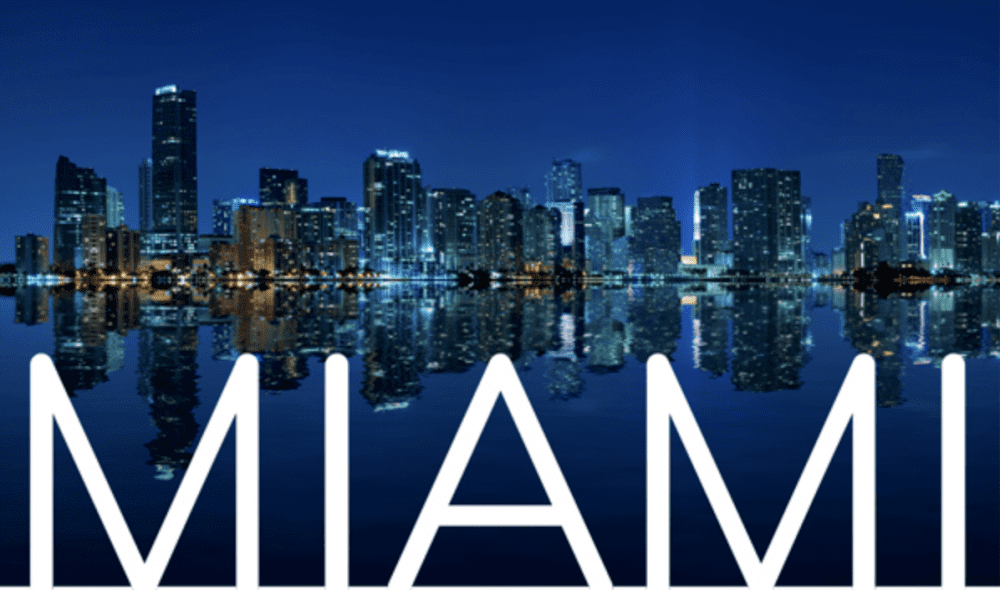 "buildings reflected in the water and below it is the text ""MIAMI"""