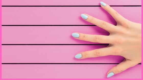 hand with beautiful nails on a pink background